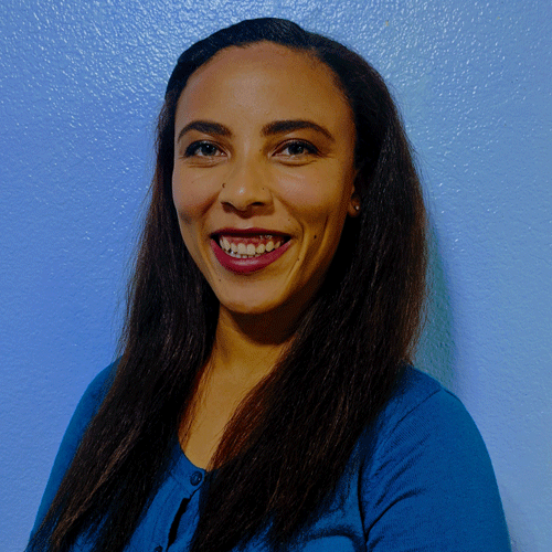 headshot of bi-racial woman on a blue background, She is smiling has long dark brown hair tan skin and pink lipstick wearing a blue shirt .