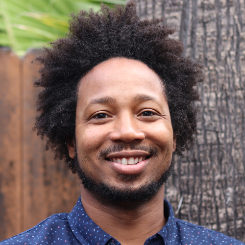 headshot avatar of smiling black male wearing a green shirt