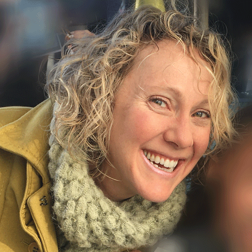 headshot of caucasian woman with short curly blond hair smiling. She is wearing an tan coat and a cream chunky scarf.